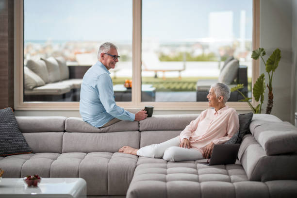 gerne älteres paar in den komfort von ihrem wohnzimmer miteinander zu reden. - seniorenwohnungen stock-fotos und bilder