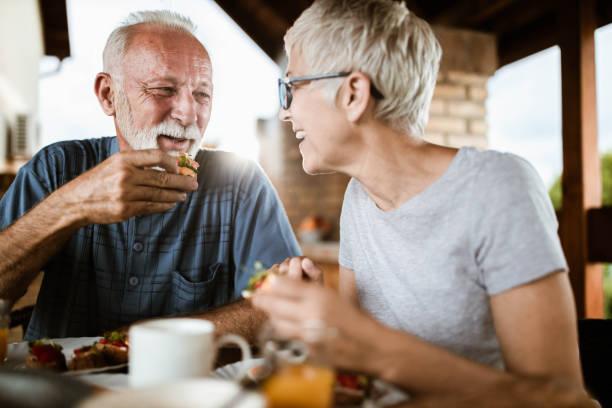 feliz pareja madura hablando mientras desayuna en un balcón. - couple lunch outdoors fotografías e imágenes de stock