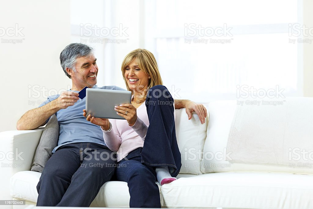 Happy mature couple together with credit card and digital table royalty-free stock photo