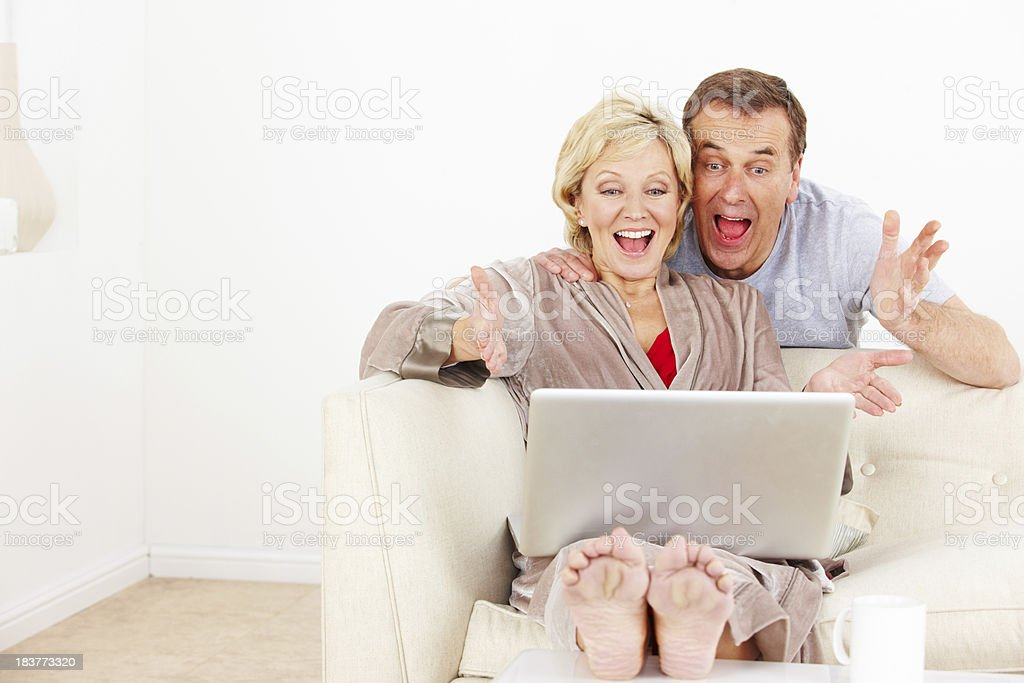 Happy mature couple using laptop in lounge royalty-free stock photo