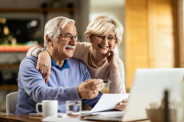 Happy mature couple using laptop while planning their home budget. Happy senior couple going through home finances and using computer at home. senior couple stock pictures, royalty-free photos & images