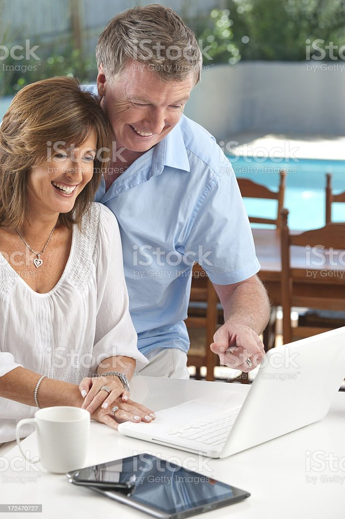 Happy mature couple using wireless technology royalty-free stock photo