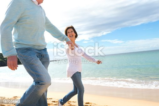 635845698istockphoto Happy mature couple walking along the beach 187054983