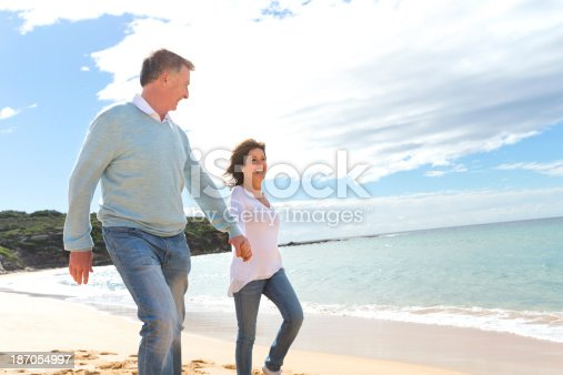 635845698istockphoto Happy mature couple walking along the beach 187054997