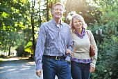Portrait of happy mature couple walking together in a park