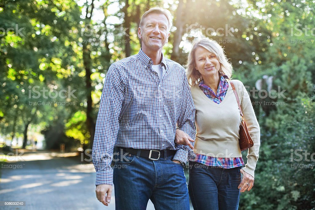 Happy mature couple walking in a park stock photo