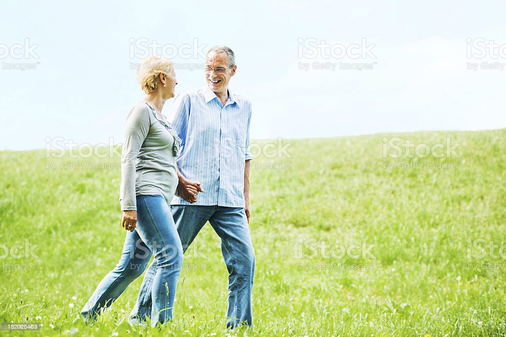 Happy mature couple walking in the field. royalty-free stock photo
