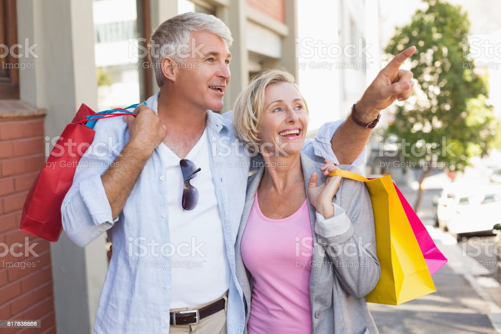 Happy mature couple walking with their shopping purchases stock photo