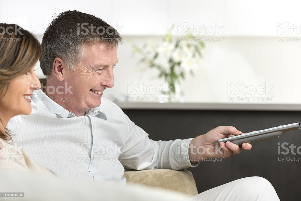 Happy mature couple watching TV royalty-free stock photo