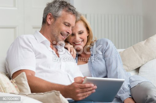 638771390istockphoto Happy Mature Couple With Tablet 507004997
