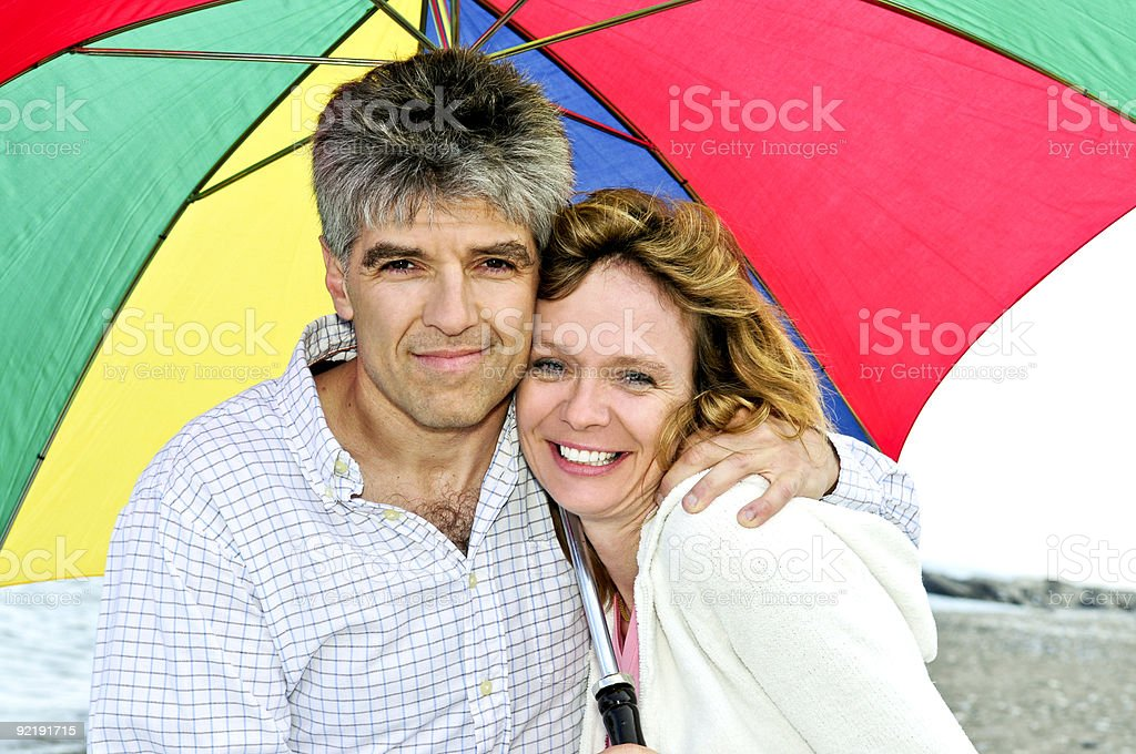 Happy mature couple with umbrella stock photo