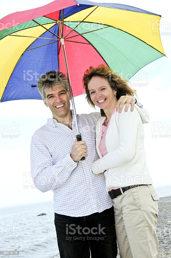 Happy mature couple with umbrella royalty-free stock photo