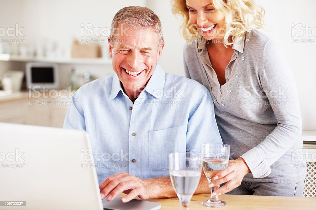 Happy mature couple with wineglasses using laptop in kitchen royalty-free stock photo