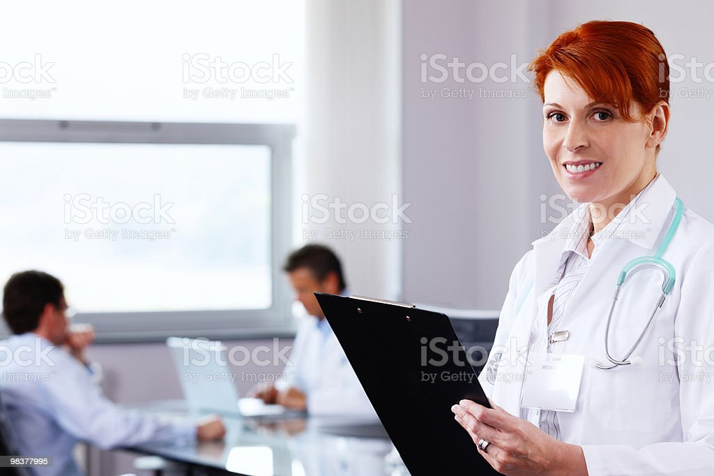 Happy mature female Doctor holding clipboard while working with colleagues royalty-free stock photo