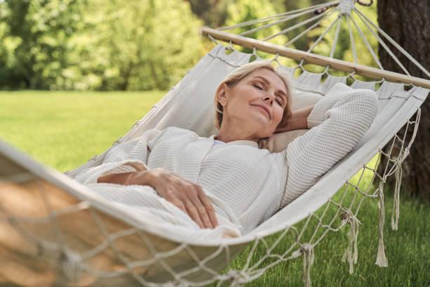 Happy mature female sleeping in hammock outdoors stock photo