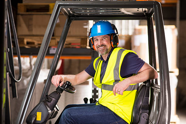happy mature forklift truck driver smiling to camera stock photo