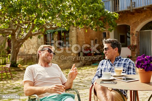 Smiling friends talking while sitting in yard. Happy men are having leisure time. They are wearing casuals.