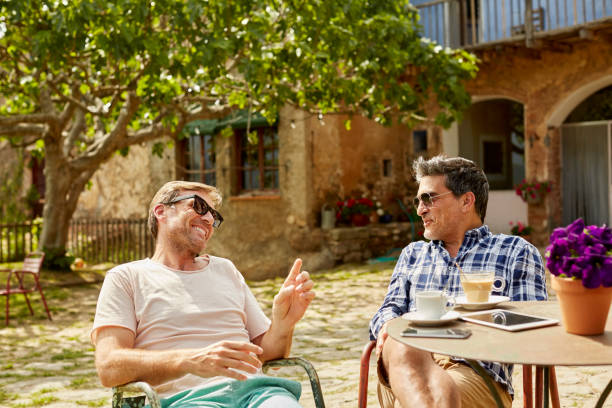 Happy mature friends talking while sitting in yard stock photo