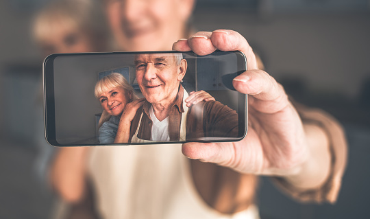 Happy mature husband and wife making selfie on phone