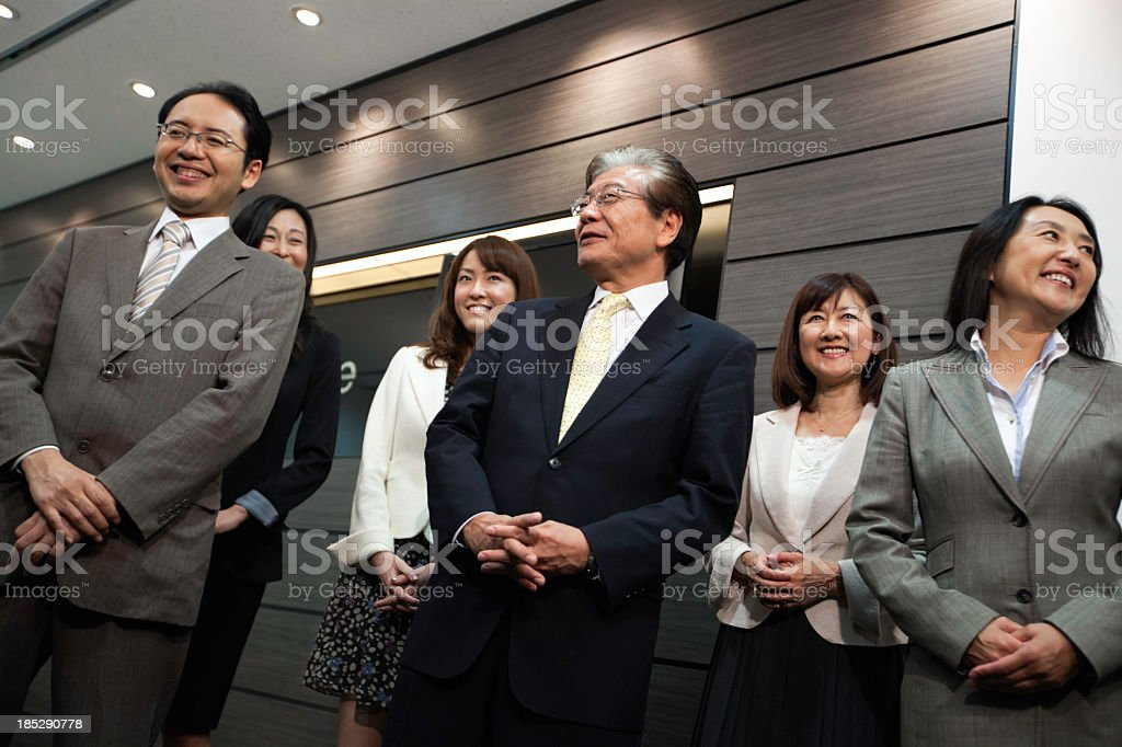 Happy mature Japanese businessman with his team in corporate interior royalty-free stock photo