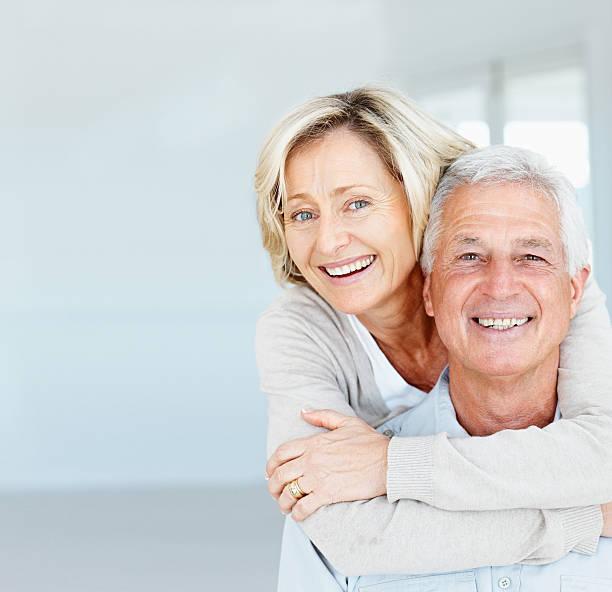 happy mature lady hugging her husband from behind - vrouw 60 stockfoto's en -beelden