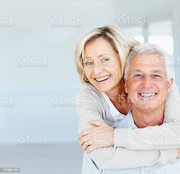 Happy Mature Lady Hugging Her Husband From Behind Stock Photo - Download Image Now