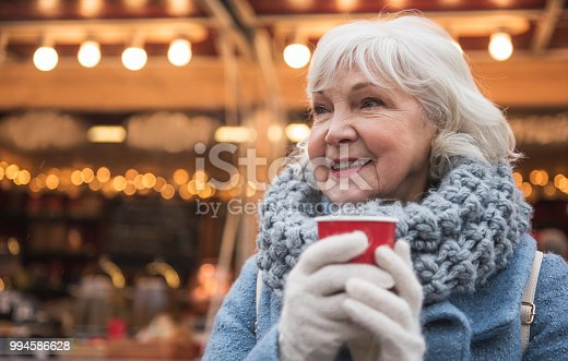 Enjoying winter holidays. Portrait of joyful senior woman drinking mulled wine with pleasure. She is standing on street and smiling. Copy space