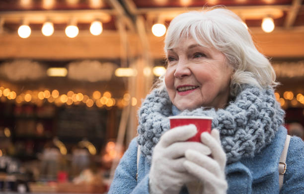 Happy mature lady warming up by hot beverage outdoor stock photo