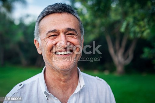 Happy mature male man smiling at the park