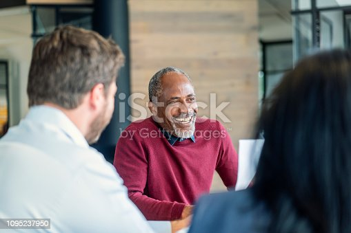 Smiling mature male manager sitting with colleagues in board room. Multi-ethnic professionals are planning strategy during meeting. They are at new office.