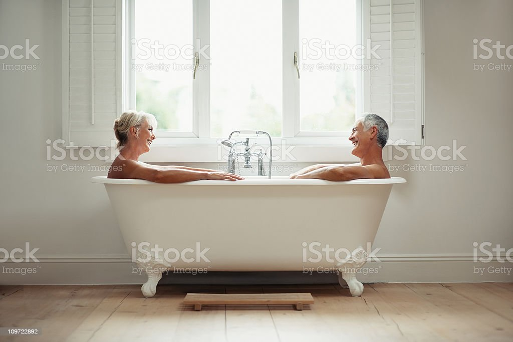 Happy mature man and woman in a bathtub royalty-free stock photo