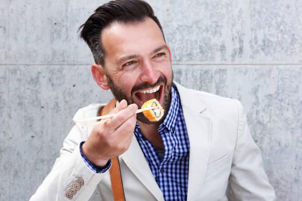 glücklicher reifer mann isst sushi - sushi essen stock-fotos und bilder