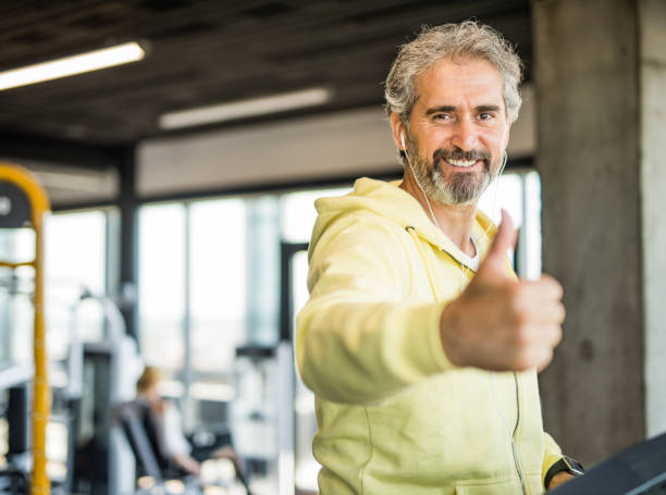 Happy mature man exercising in the gym and showing thumb up. stock photo