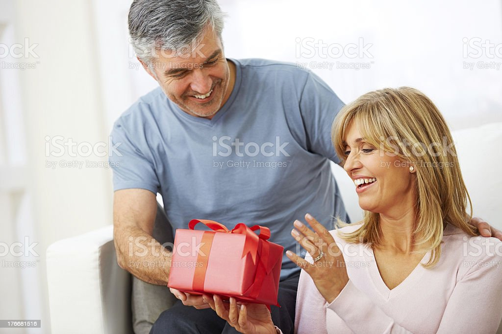 Happy mature man giving birthday gift to his wife royalty-free stock photo