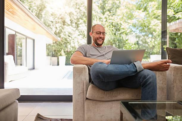 glücklich älterer mann mit video, am laptop - lässiges wohnzimmer stock-fotos und bilder