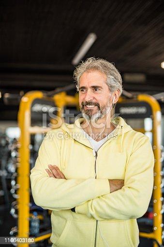 Happy mature man hits the gym on a regular basis.