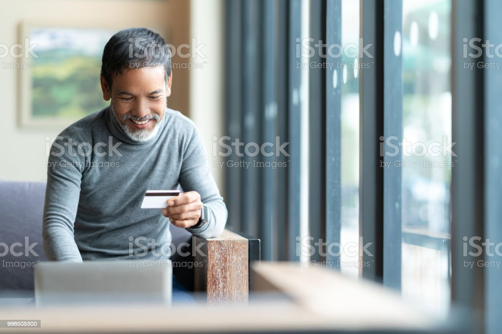 Happy mature man holding credit card paying online by using laptop...