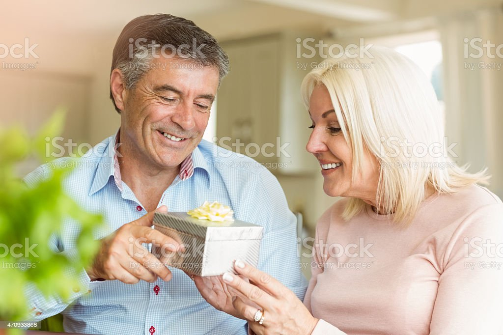 Happy mature man offering wife a gift stock photo