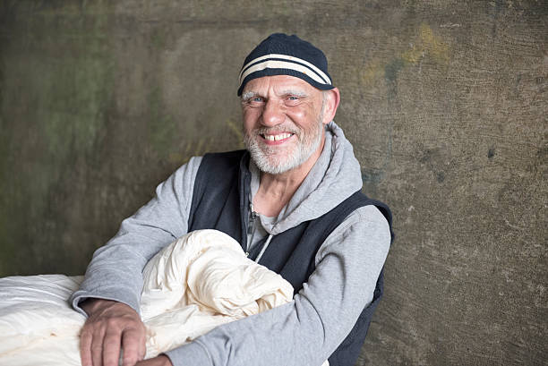 happy mature man outdoors with a blanket - homelessness stock photos and pictures