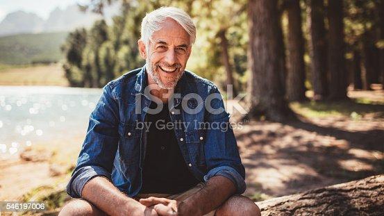 istock Happy mature man sitting near a lake 546197006