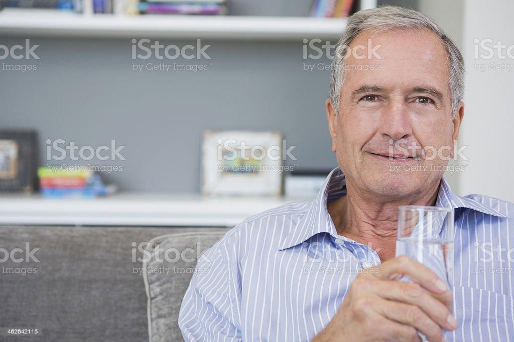 Happy mature man sitting on his sofa drinking water stock photo