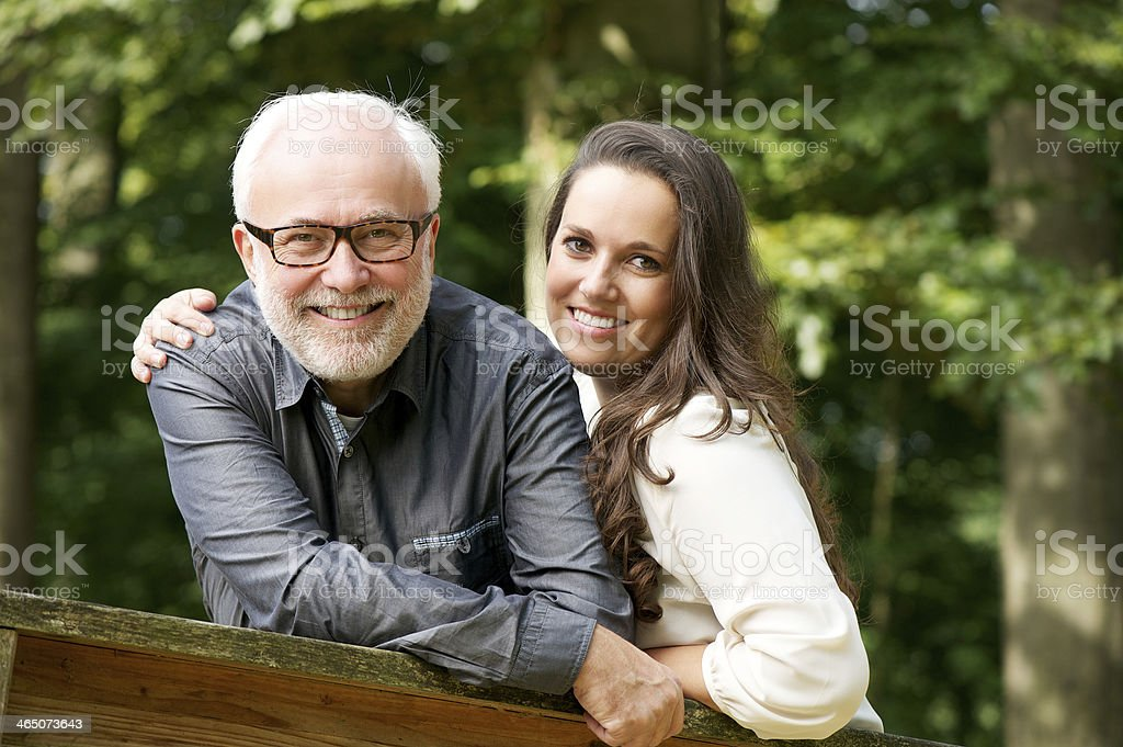 Happy mature man smiling with young woman stock photo