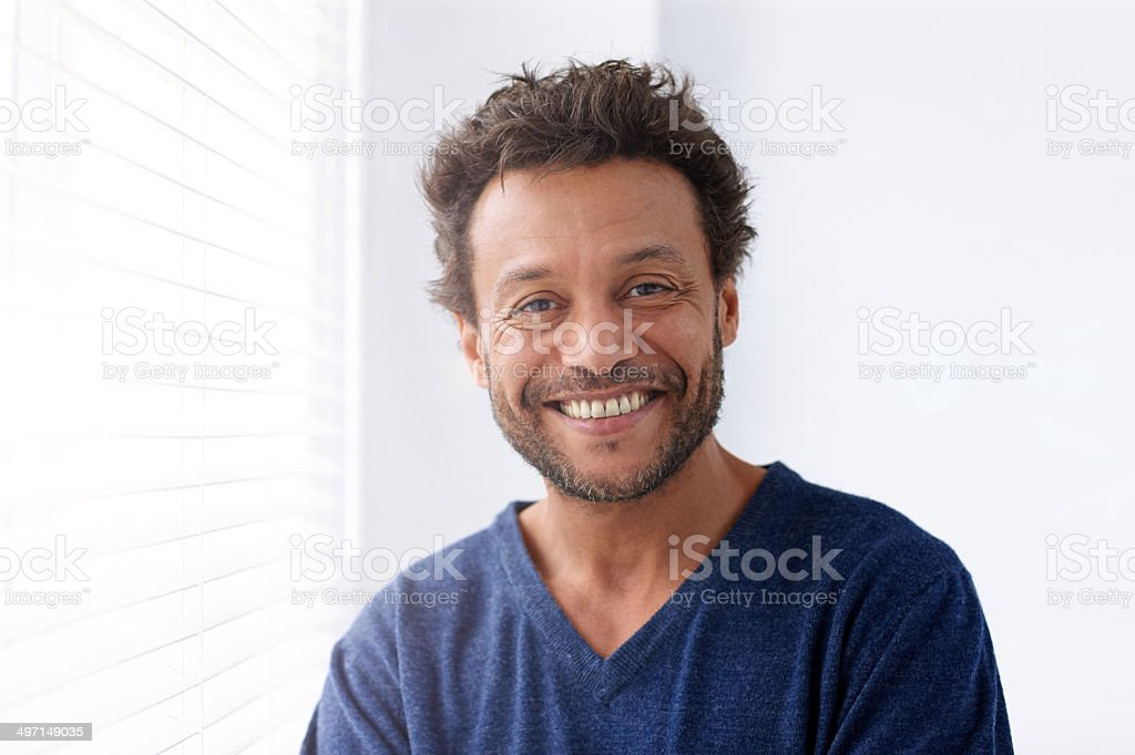 Happy mature man standing by a window stock photo