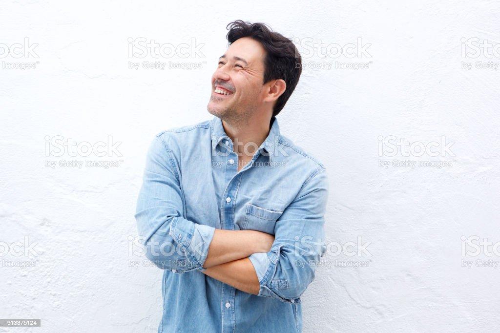 heureux homme mûr debout avec les bras croisés contre le mur blanc et à la recherche. - Photo
