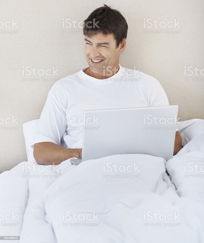 Happy mature man using a laptop on bed royalty-free stock photo