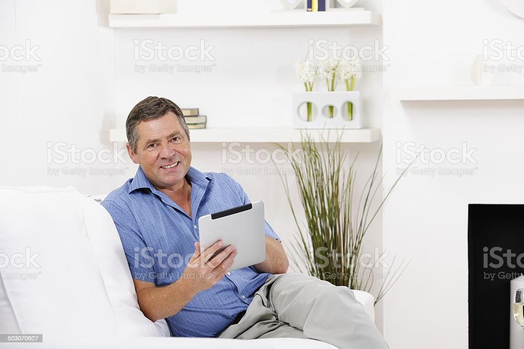 Happy Mature Man Using Digital Tablet In The Living Room stock photo