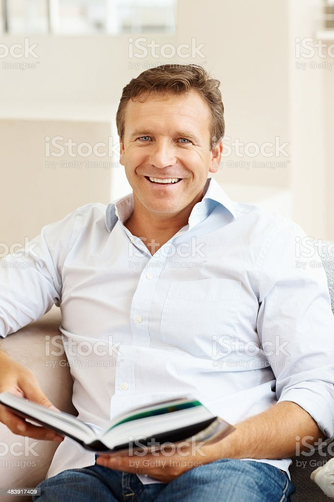 Happy mature man with book at home royalty-free stock photo