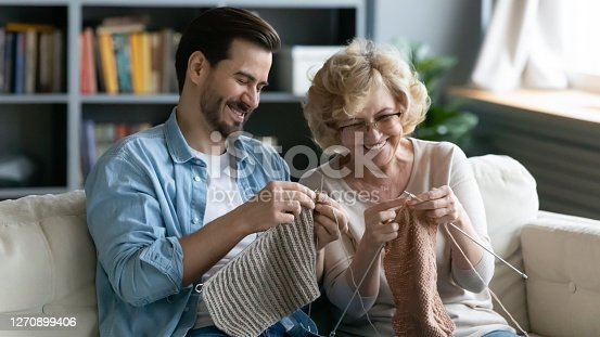 Happy mature mother and son knitting together, enjoying leisure time at home, smiling middle aged woman wearing glasses and young man sitting on cozy couch in living room, holding needles