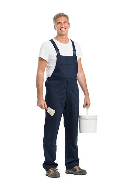 Happy Mature Painter Portrait Of Happy Mature Painter Looking at Camera Isolated On White Background bib overalls stock pictures, royalty-free photos & images
