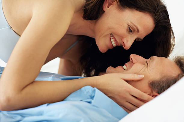 Happy mature passionate couple together in bed stock photo